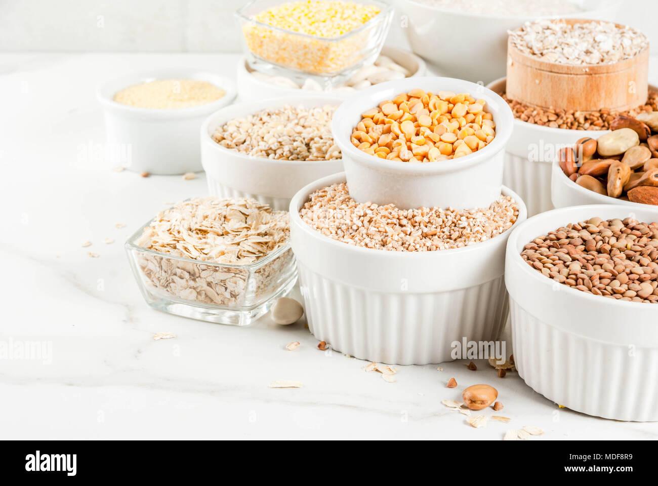 Différents types de sélection de céréales Gruaux dans différents bol sur fond de marbre blanc, copy space Banque D'Images