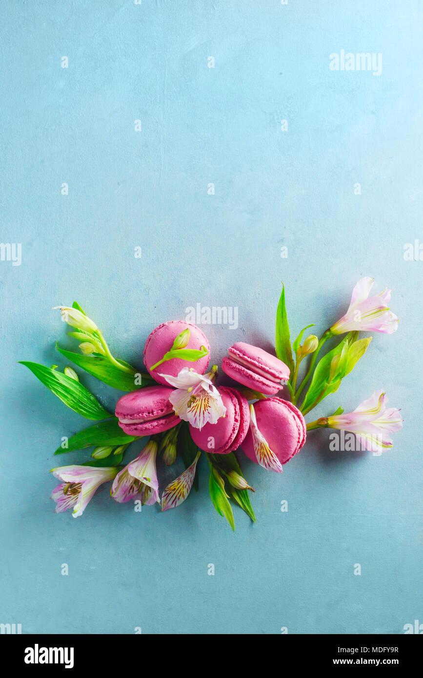 Macarons français sur une vignette avec arrière-plan concret d'alstroemeria printemps fleurs. Photographie dessert avec copie espace. Photo Stock