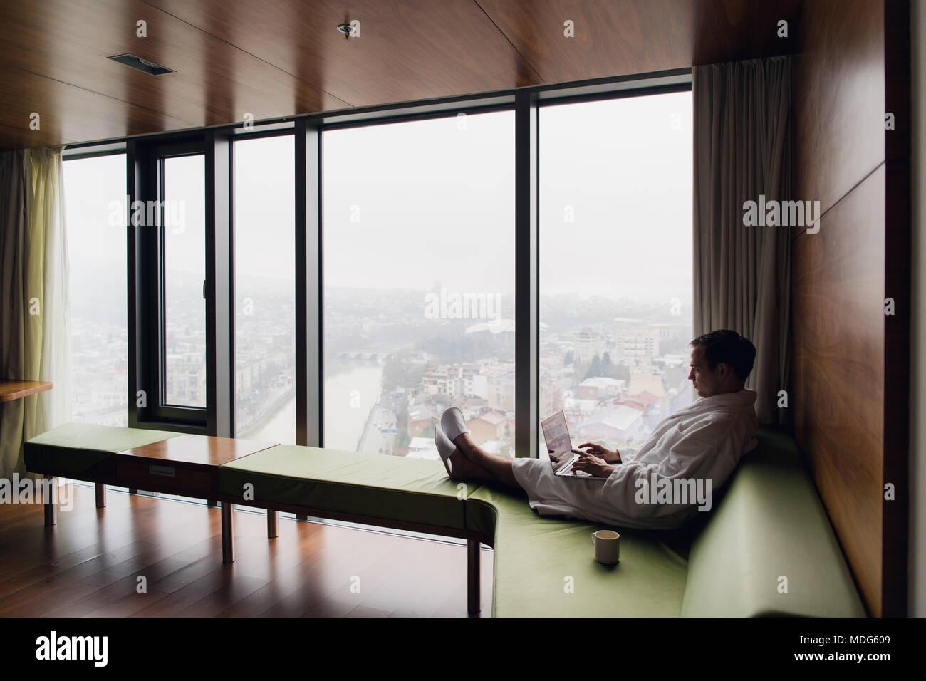 Homme séduisant appréciant son café du matin sur son ordinateur à sa chambre d'hôtel Photo Stock