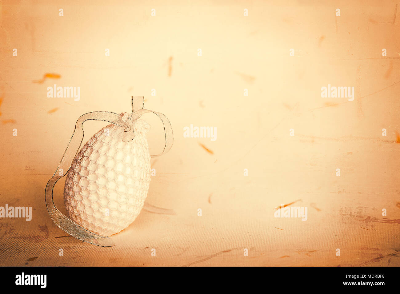 Oeuf de Pâques blanc en crochet sur papier artisanal avec texture grunge fond pétales. Shallow DOF. Banque D'Images