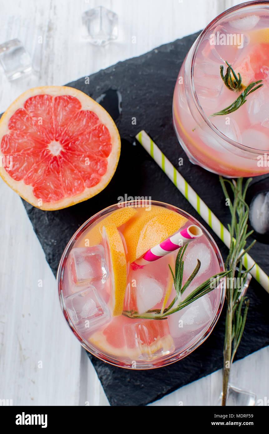 Cocktail avec de la glace et de tranches de pamplemousse, les ingrédients pour un verre sur une table en bois blanc, copy space Photo Stock