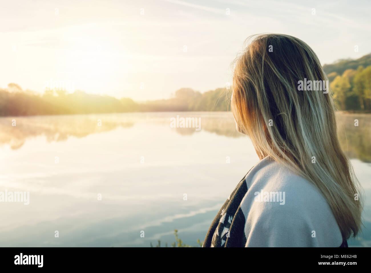 Jeune femme contemplant la nature par le lac au lever du soleil, le printemps, la France, l'Europe. Les gens voyagent de détente dans la nature concept. L'image des tonalités Photo Stock