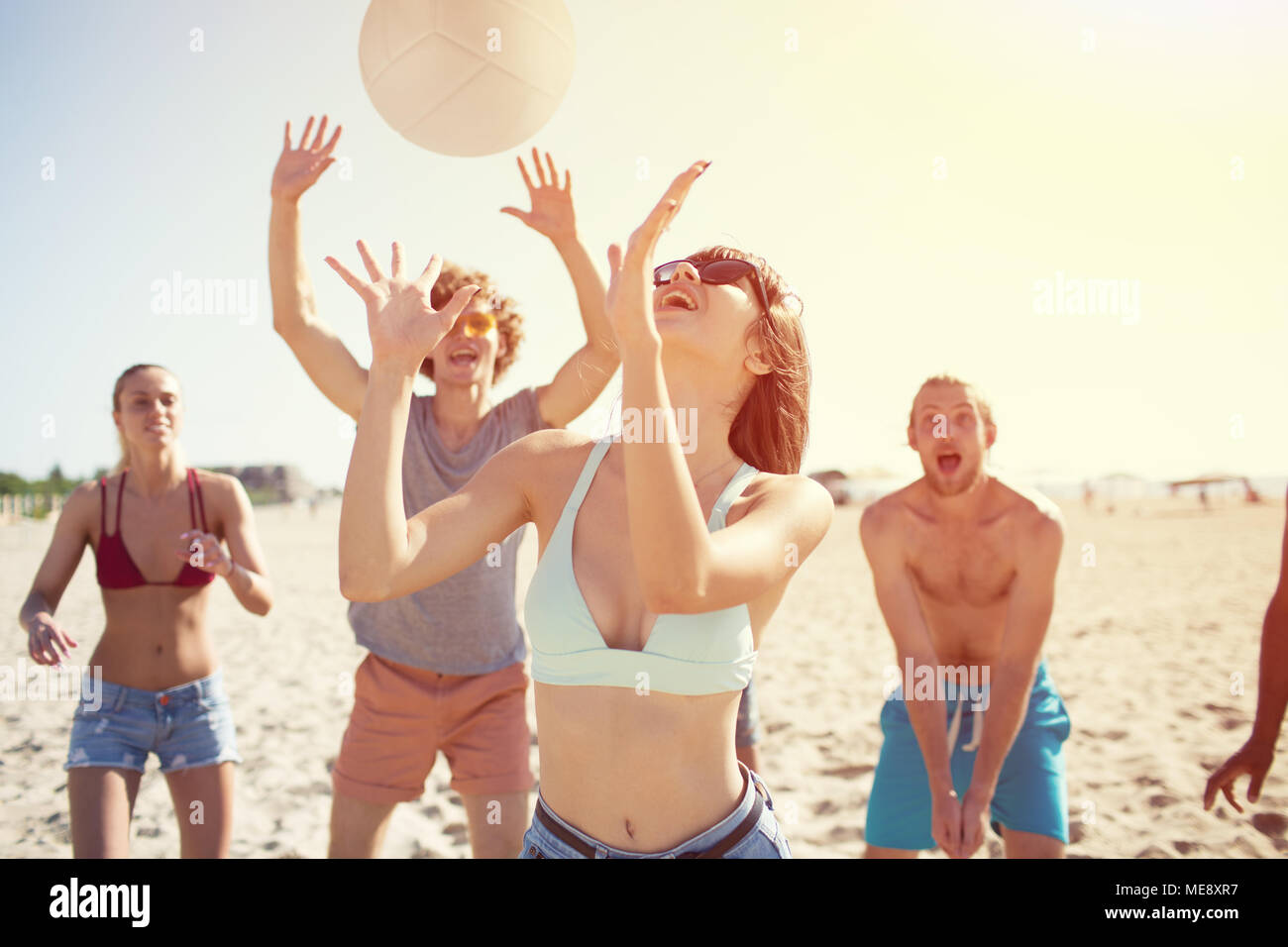 Groupe d'amis jouant au beach-volley sur la plage Photo Stock