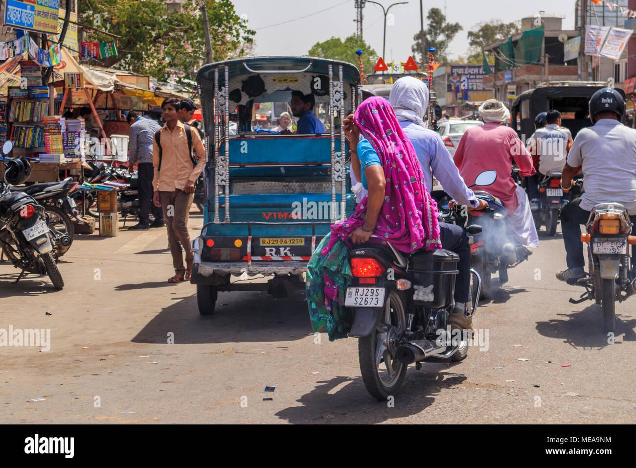 Scène de rue à Dausa, Rajasthan, Inde du nord, une femme de la région à cheval sur une moto avec leurs couleurs locales typiques et vêtements Coiffure voile Photo Stock