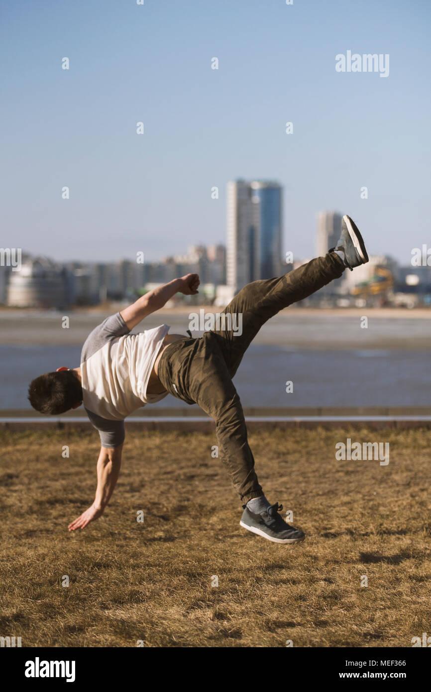 Jeune homme sportif parkour effectue des sauts acrobatiques devant skyline Photo Stock