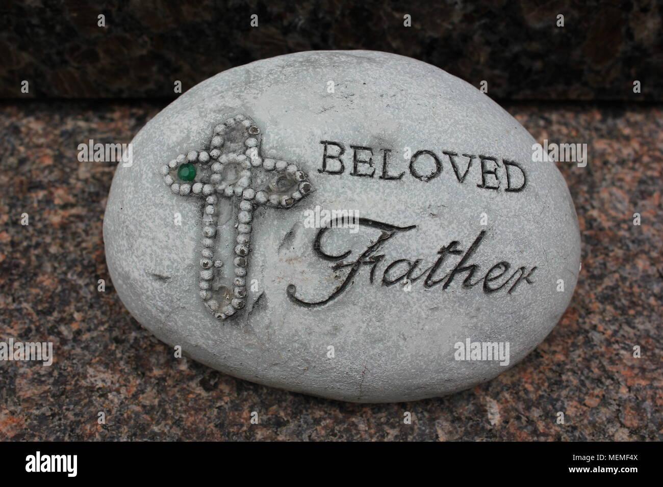 """Rock Memorial qui indique: """"Cher Père"""" à côté d'une croix décorée. Photo Stock"""