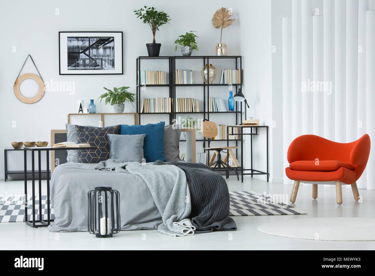 Fauteuil orange à côté du lit dans la chambre grise avec intérieur ...