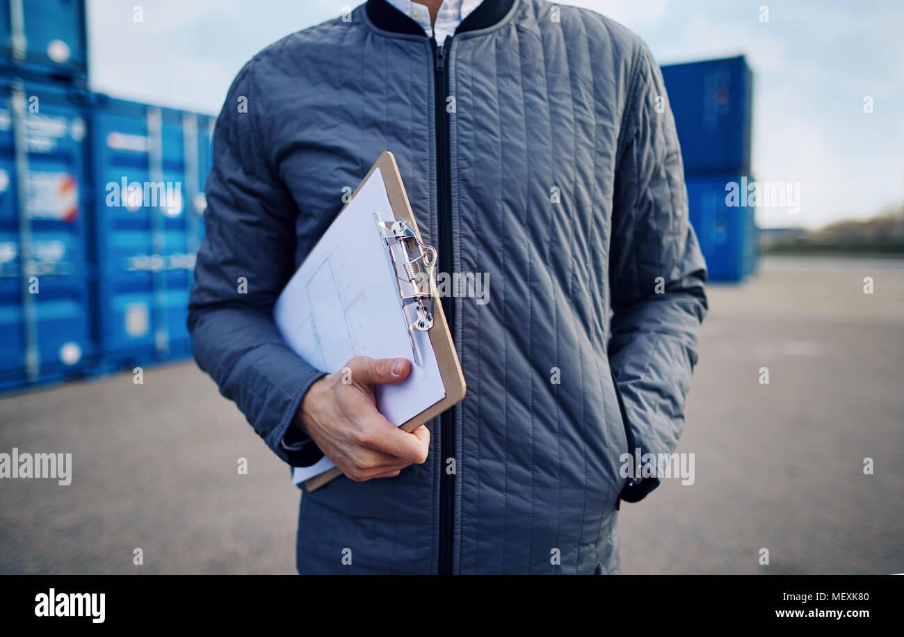 Libre d'un contremaître de triage fret debout sur un quai d'expédition commerciale détenant un inventaire sur un presse-papiers Photo Stock