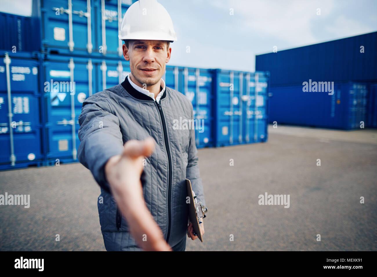 Contremaître de marchandises portant un casque de l'extension d'une poignée de main en se tenant debout sur une grande aire d'expédition commerciale détenant un presse-papiers Photo Stock