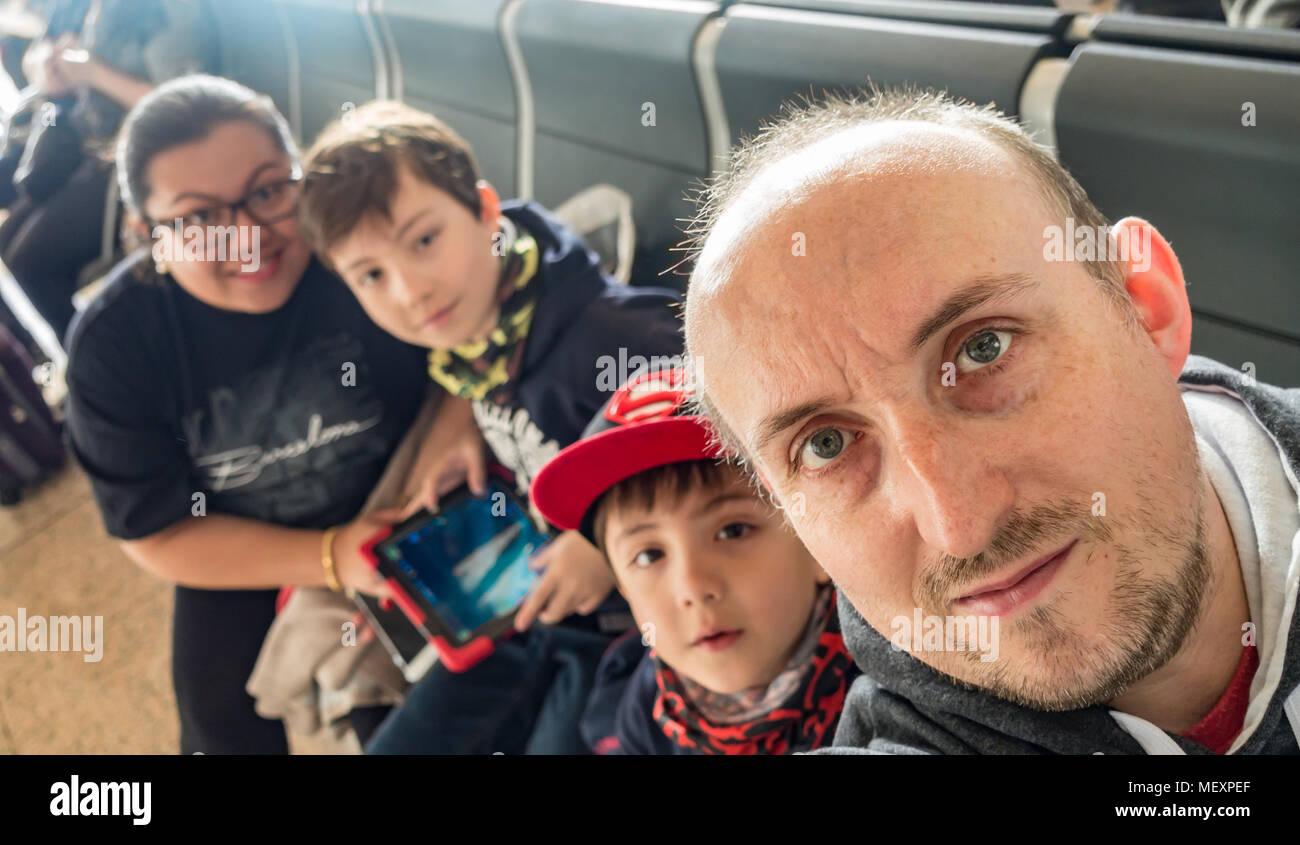 Une famille prise selfies dans la salle d'embarquement d'un aéroport. Photo Stock