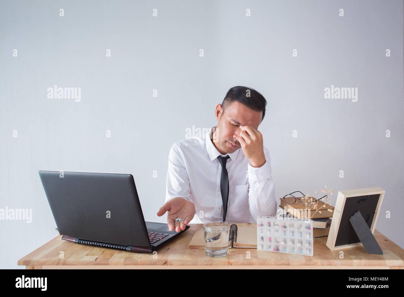 Businessman avec verre de l eau prend la pilule ronde blanche au
