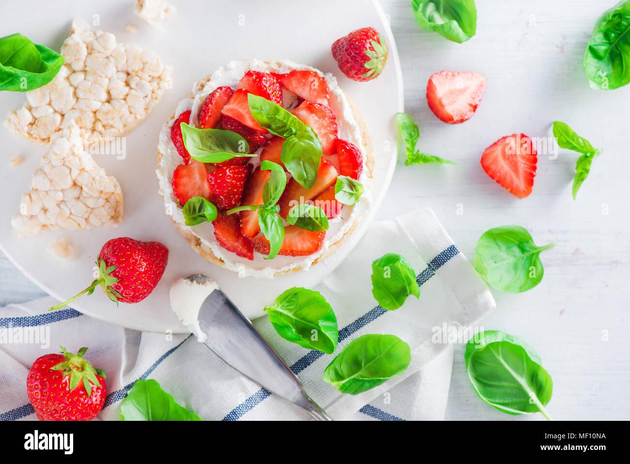 Collation santé avec des fraises fraîches, pain, fromage de chèvre, et les feuilles de basilic. Entrée facile recette. Photo Stock