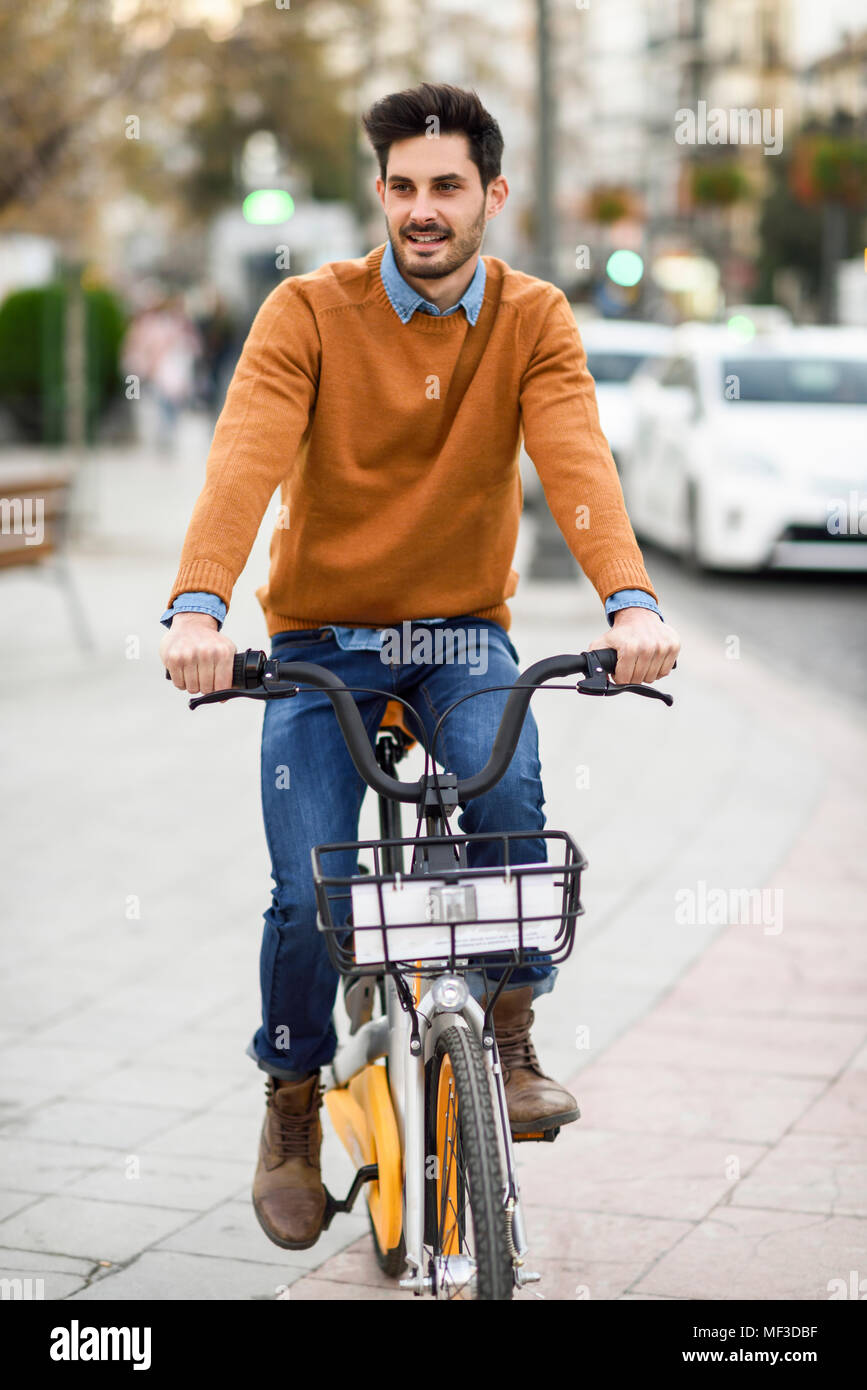 Espagne, Andalousie, Grenade. Beau jeune homme sur le partage de vélo dans la ville. Concept de vie. Photo Stock