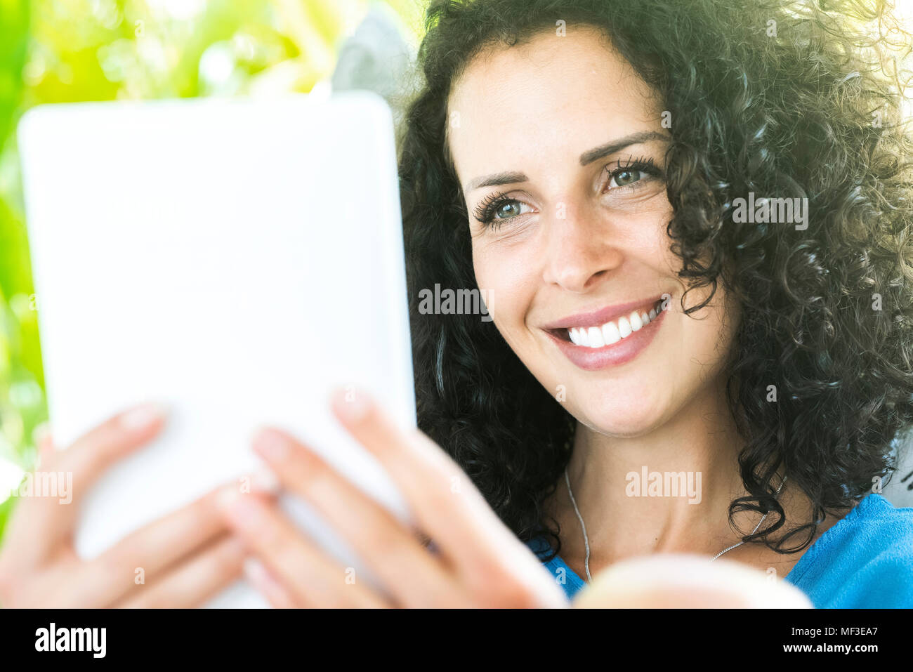 Portrait of smiling woman holding e-reader Photo Stock