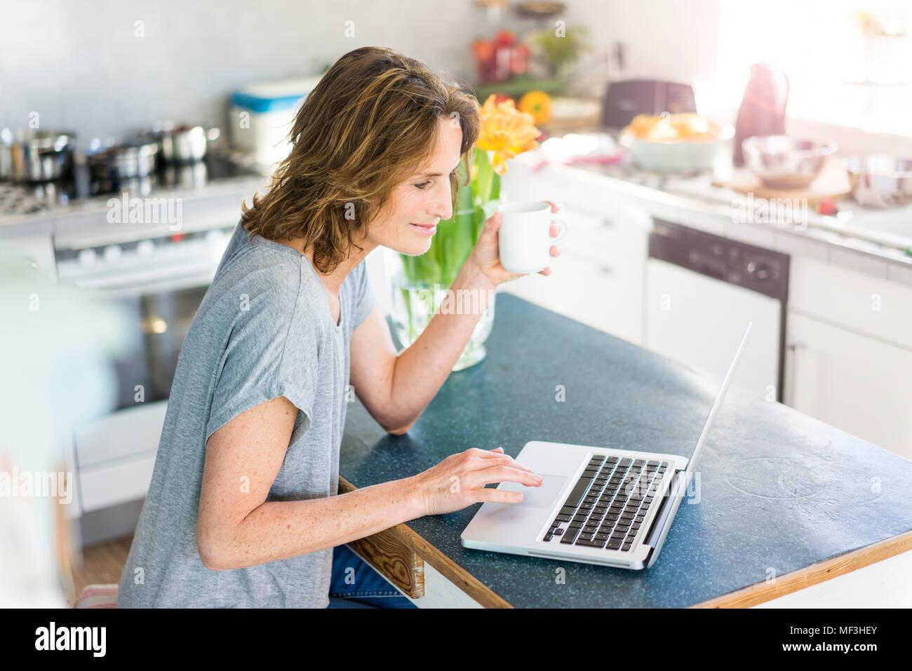 Smiling woman using laptop in cuisine à la maison Banque D'Images