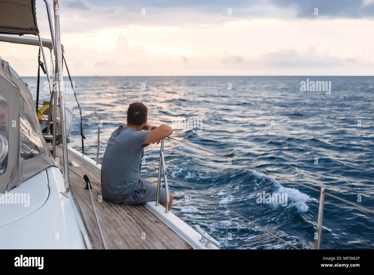 L'Indonésie, l'île de Lombok, l'homme assis sur le pont d'un bateau à voile Photo Stock
