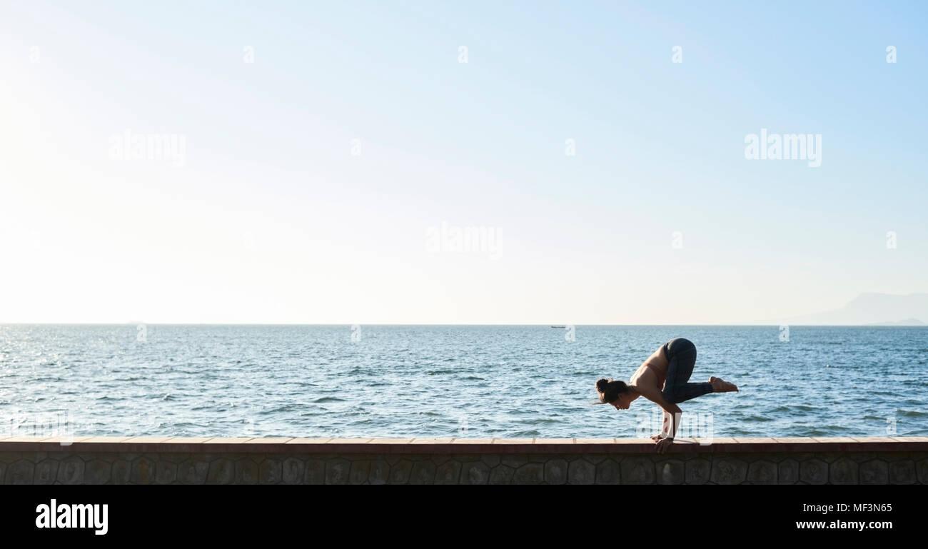 Young woman practicing yoga sur un mur par la mer Photo Stock
