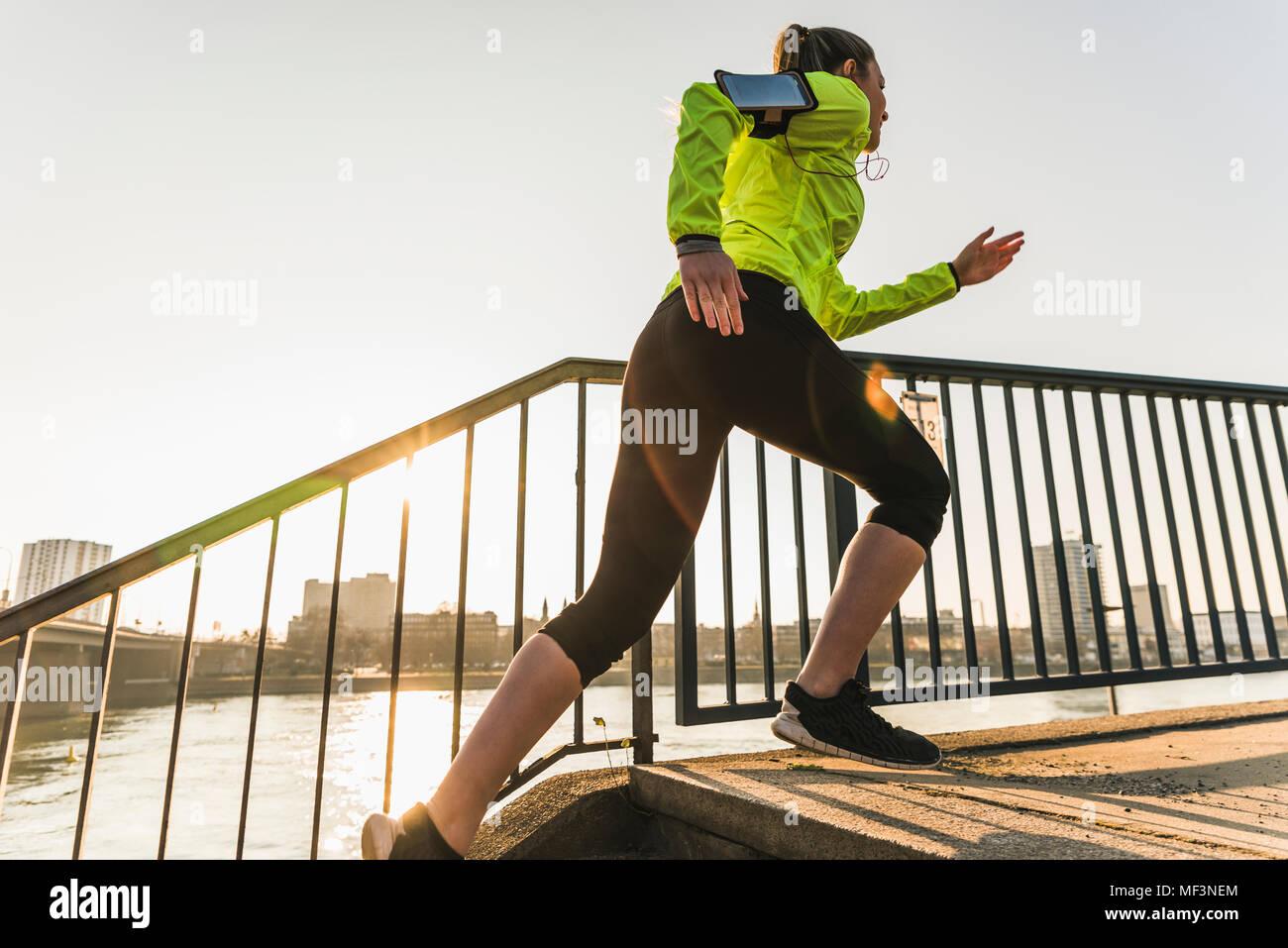 Jeune femme en marche vers le haut des escaliers à une rivière Photo Stock