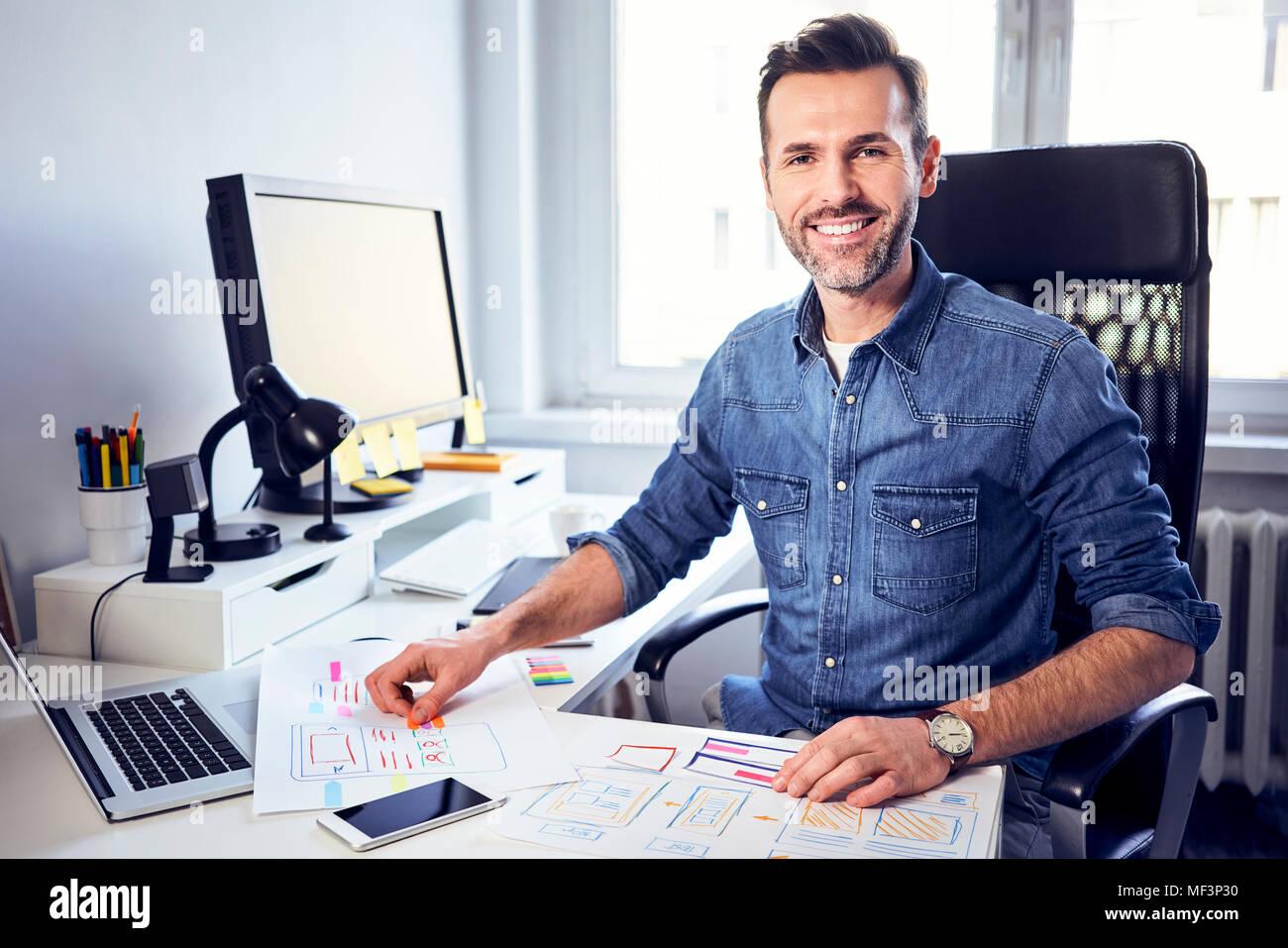 Portrait of smiling web designer travaillant sur le projet at desk in office Photo Stock