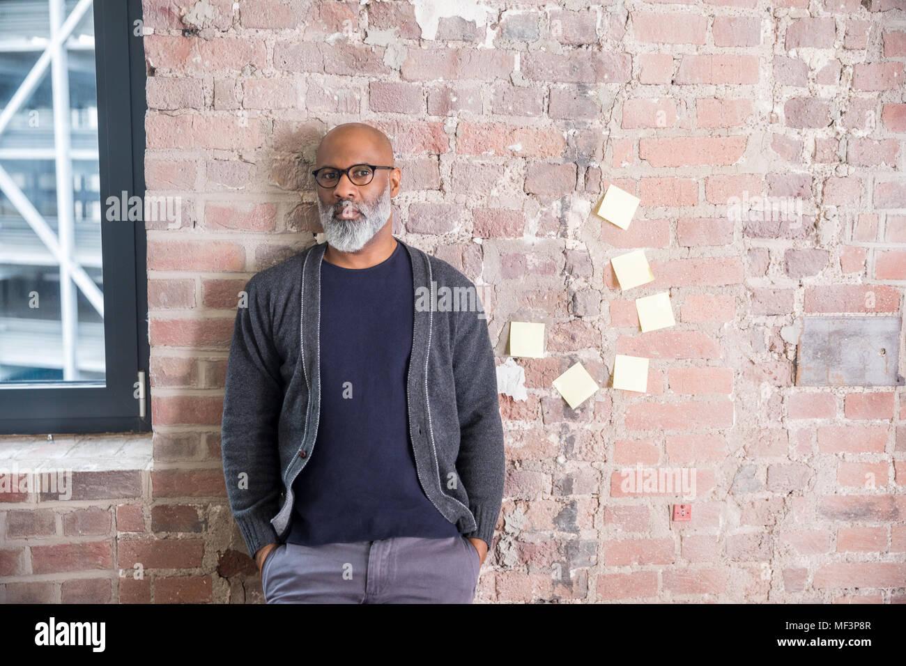 Portrait de freelancer leaning against wall dans un loft Photo Stock