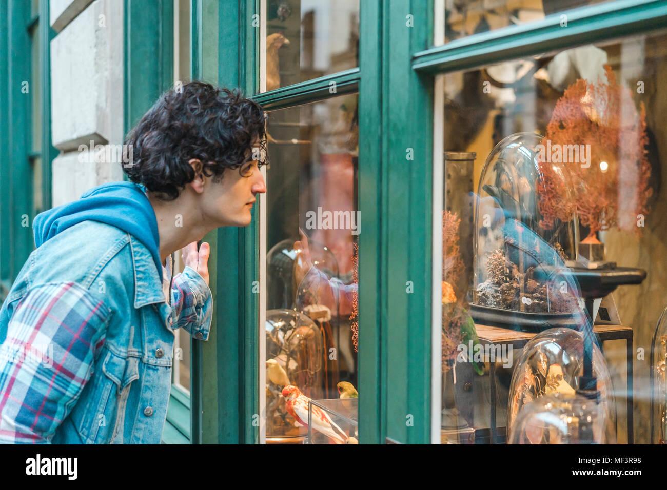 Portrait de jeune homme regardant à travers la vitre Photo Stock