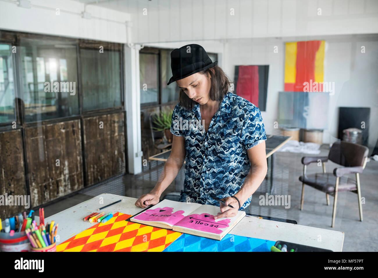 Artiste au travail, des dessins d'un ordinateur portable dans son studio de style loft avec des peintures et des œuvres d'art dans l'arrière-plan Photo Stock