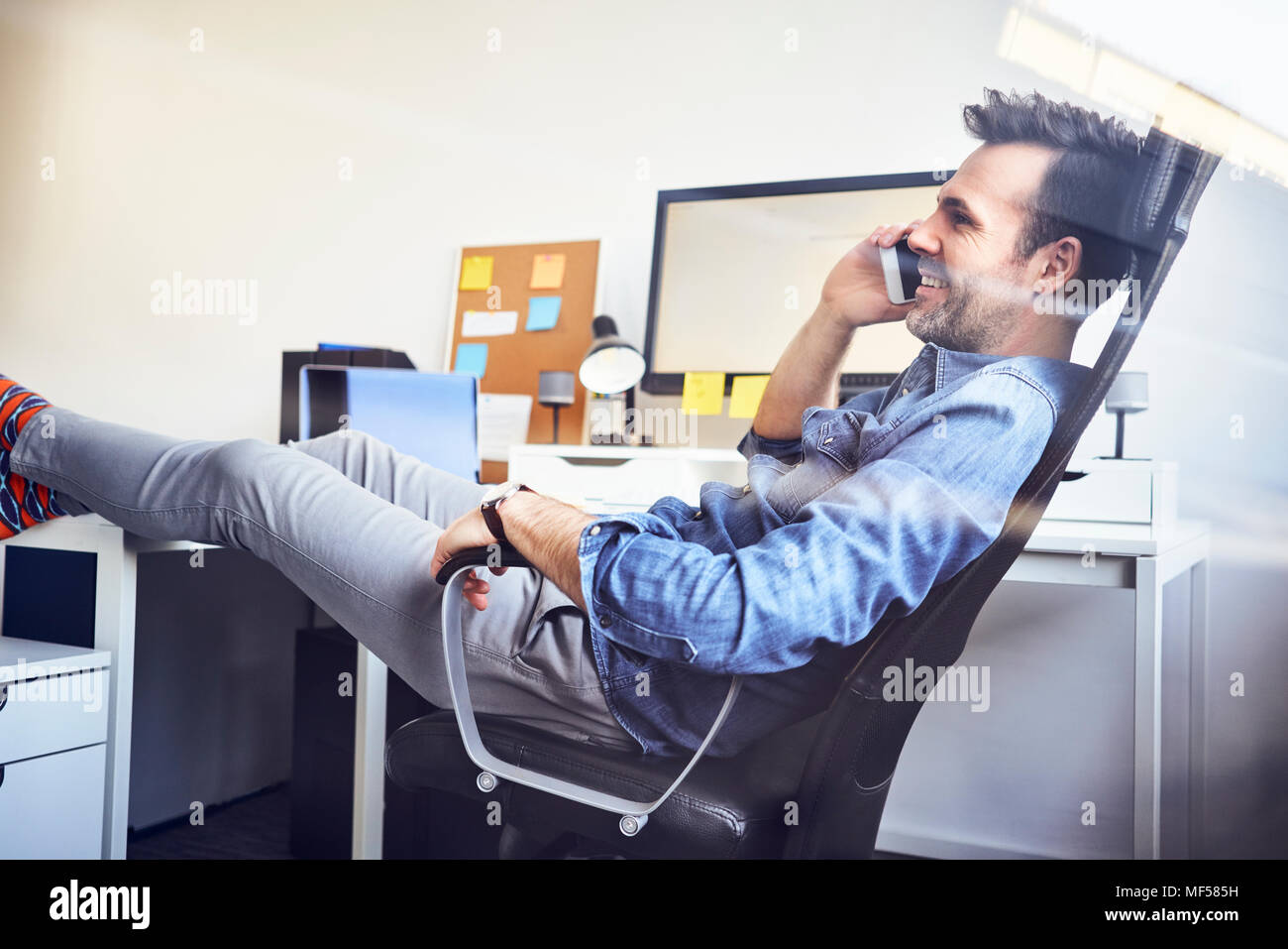 Ambiance man sitting at desk in office talking on cell phone Banque D'Images