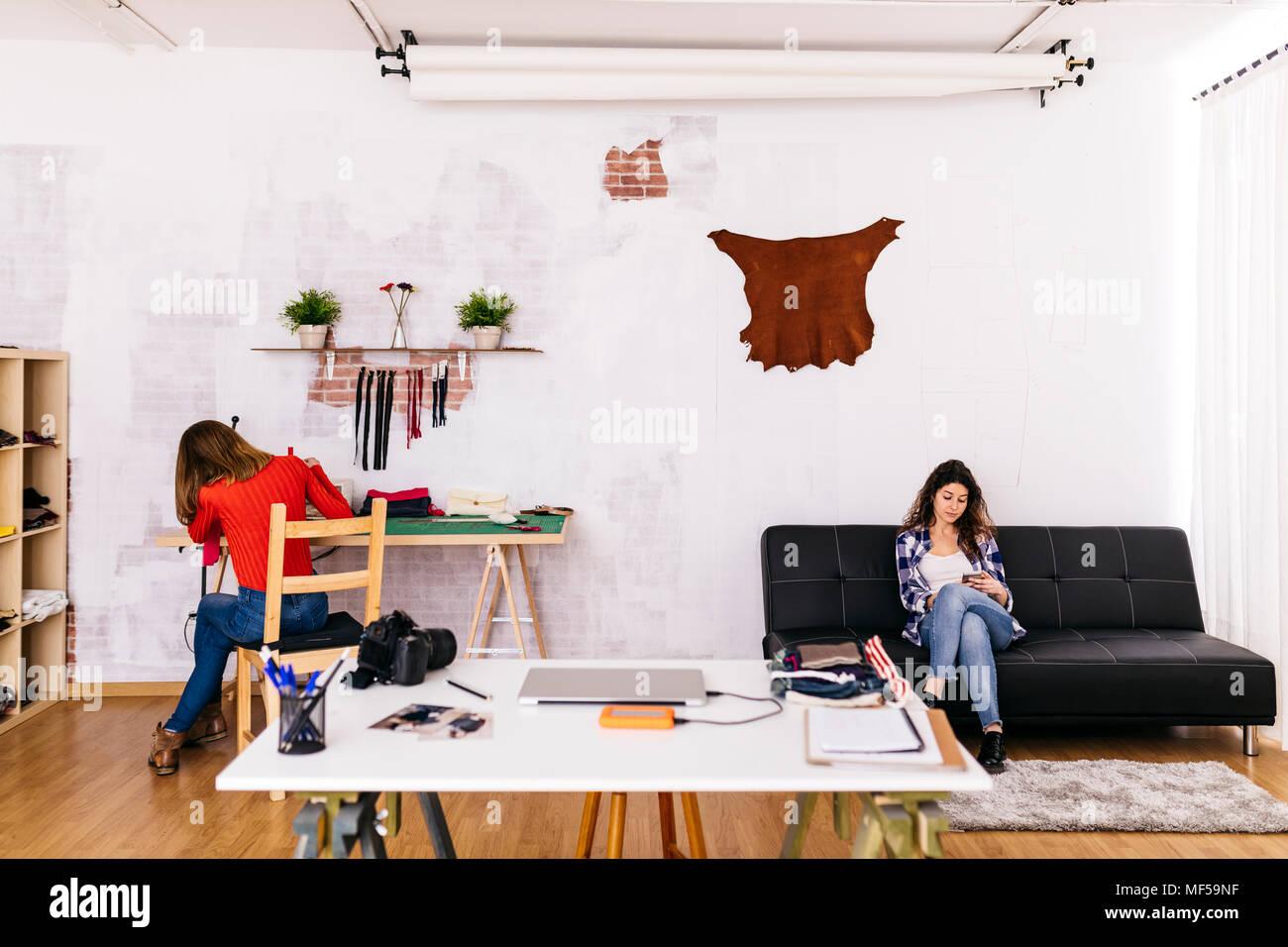 Deux femmes de la mode studio à l'aide de machine à coudre et cell phone Photo Stock