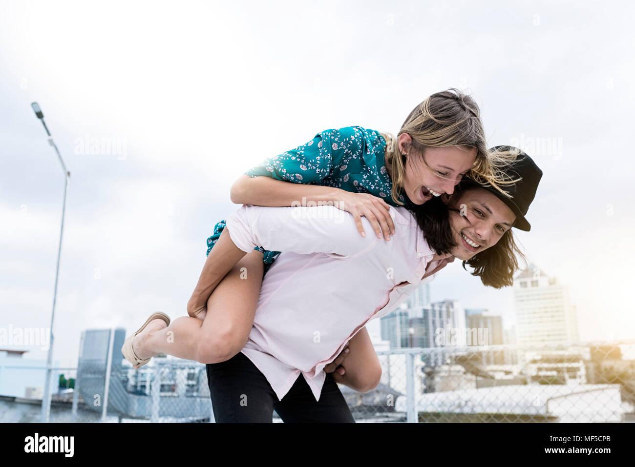 Young affectionate couple s'amuser ensemble sur le toit Photo Stock