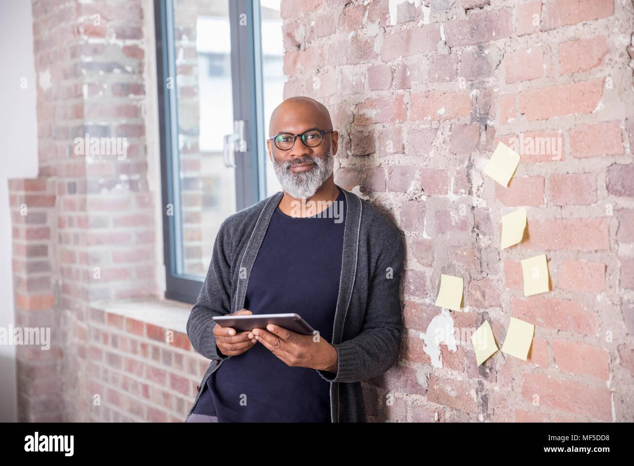 Portrait of smiling indépendant avec tablet leaning against wall dans un loft Photo Stock