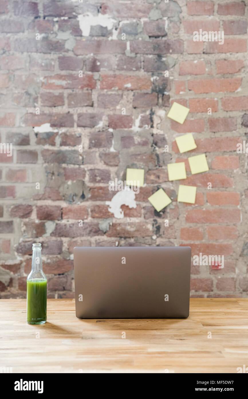Bouteille Verre de smoothie vert et ordinateur portable sur une table en bois dans un loft Photo Stock