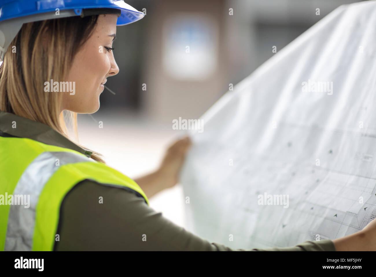 Woman wearing hard hat looking at construction plan Photo Stock