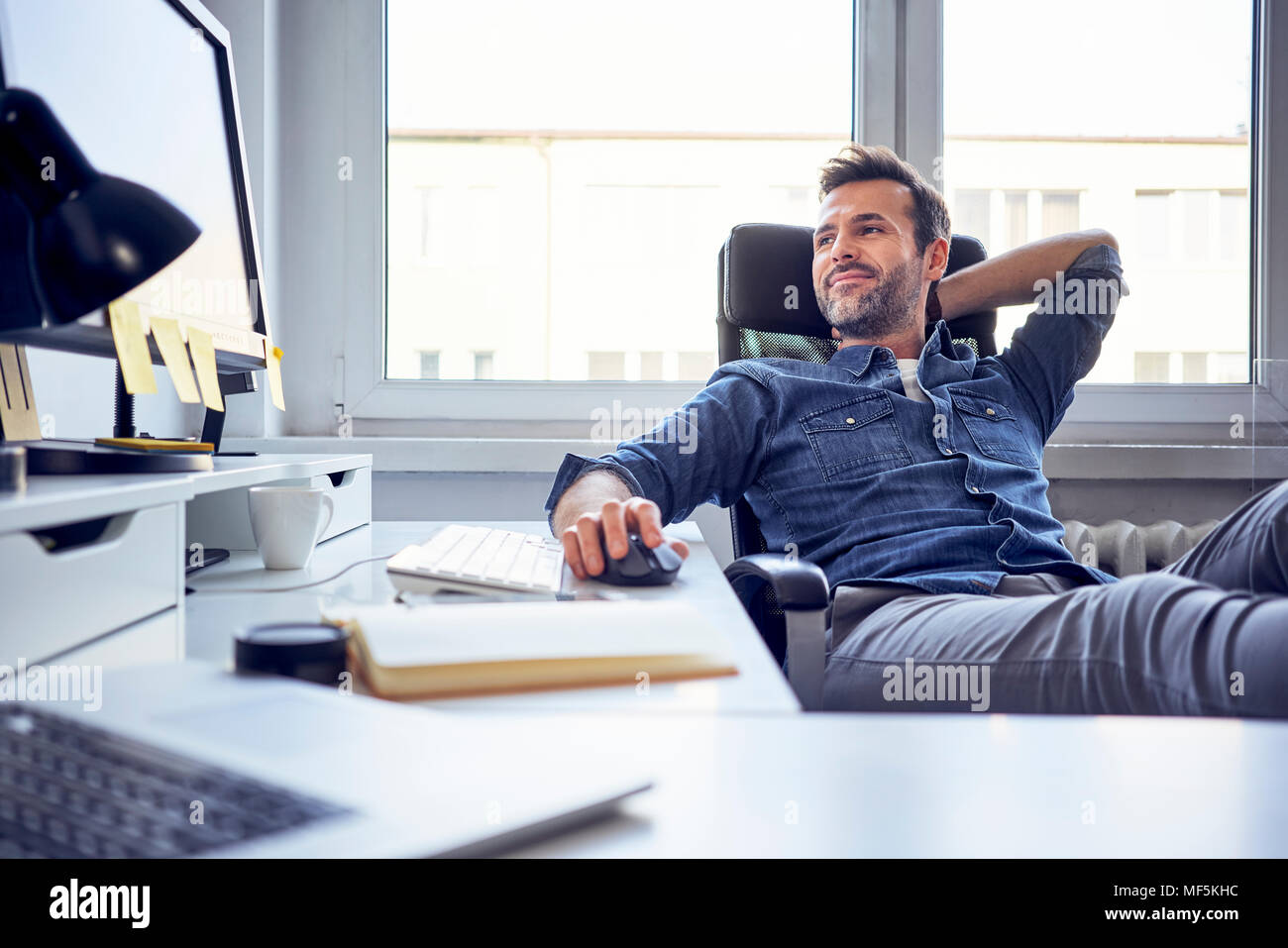 Ambiance man sitting at desk in office looking at computer screen Photo Stock