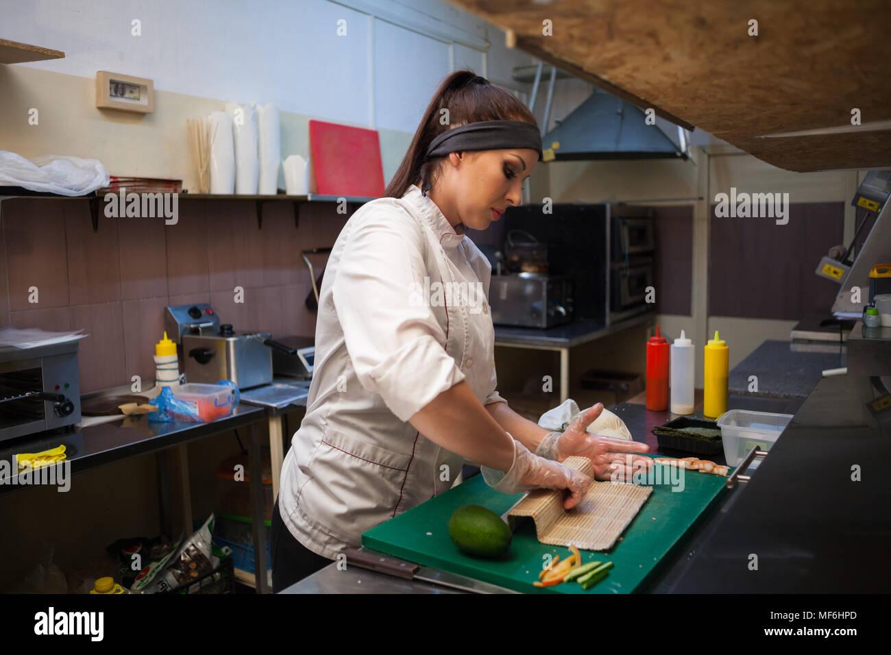 Femme en blanc chef prépare restaurant sushi Photo Stock