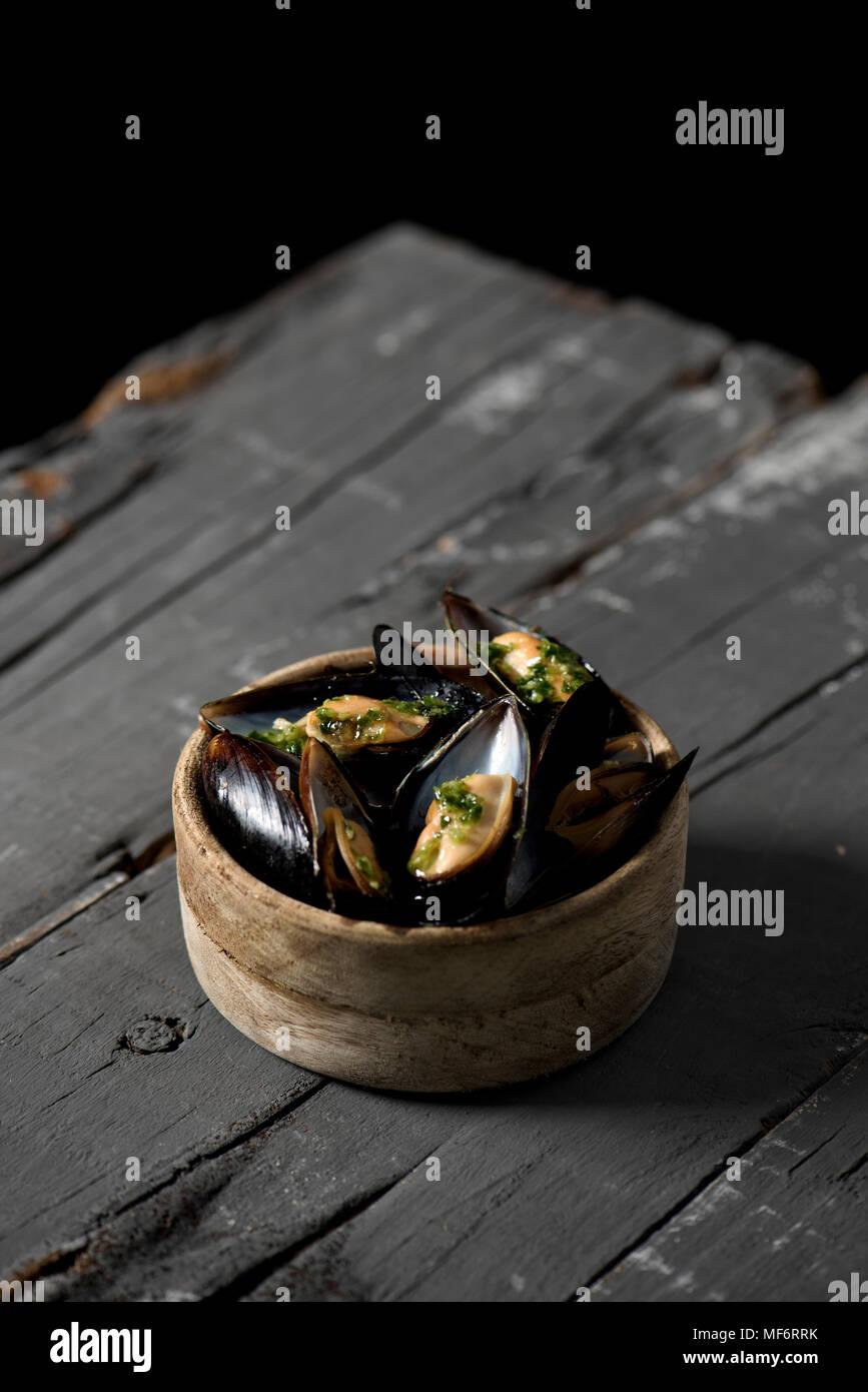 Libre d'un bol de buis avec moules marinière, une recette française de moules, sur une table en bois rustique Photo Stock
