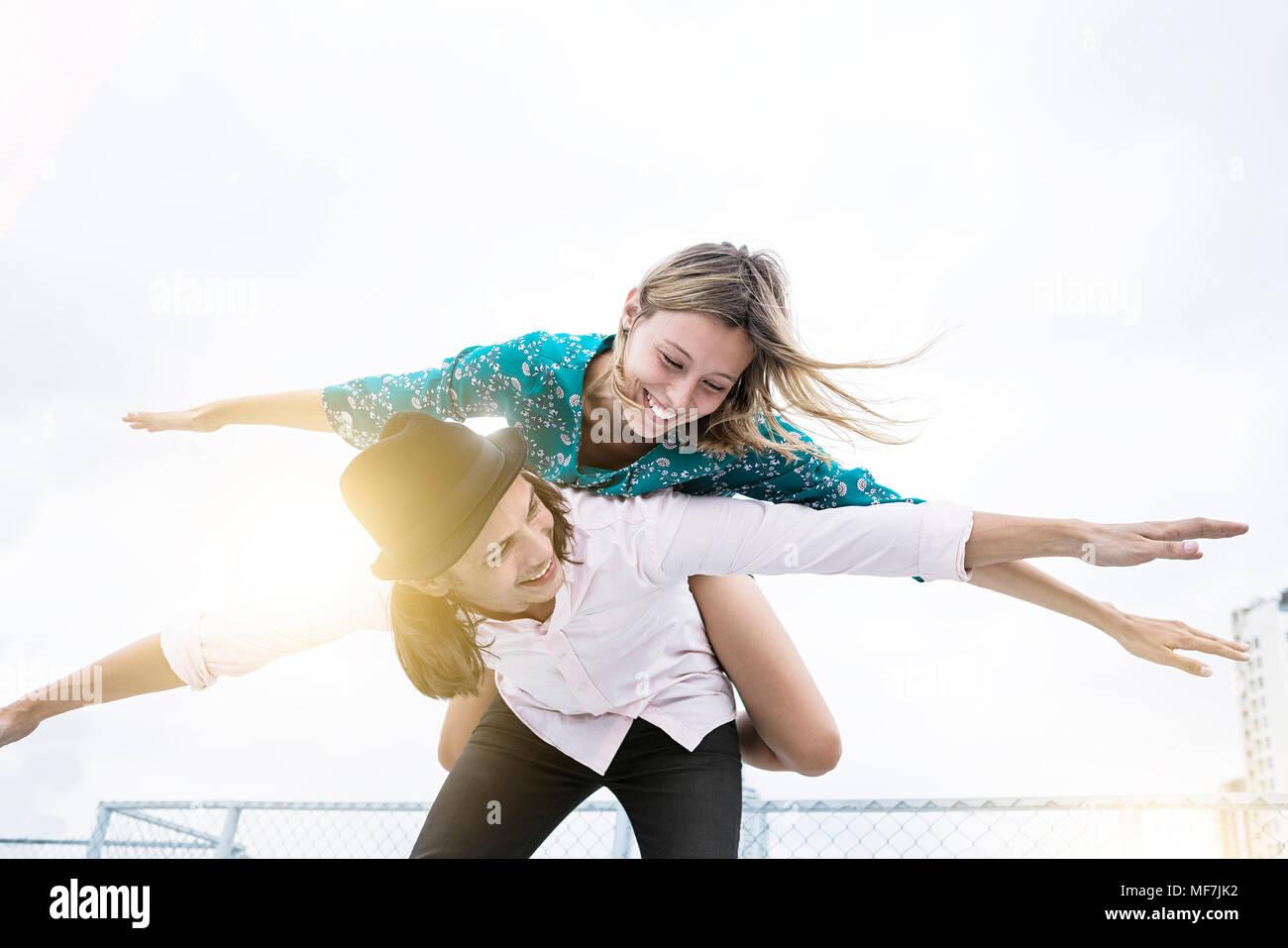 Young affectionate couple s'amuser ensemble sur le toit, en faisant semblant de voler Photo Stock