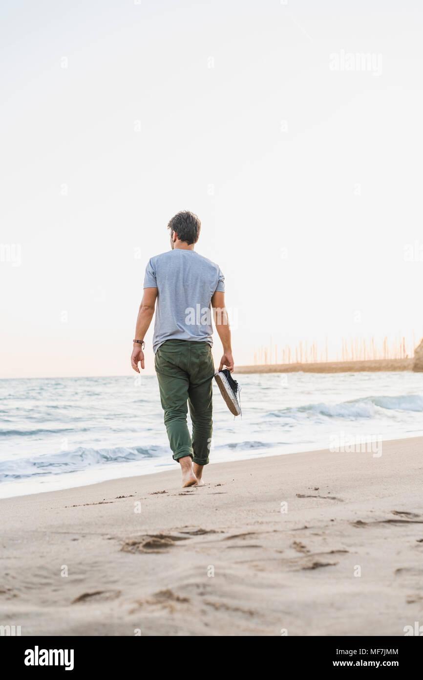 Vue arrière de l'homme marchant pieds nus sur la plage Photo Stock