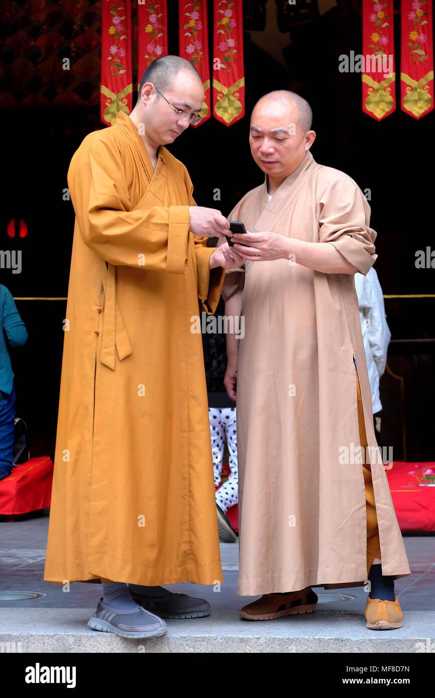 Deux moines bouddhistes avec un téléphone mobile, Temple du Bouddha de Jade, Shanghai, Chine Photo Stock
