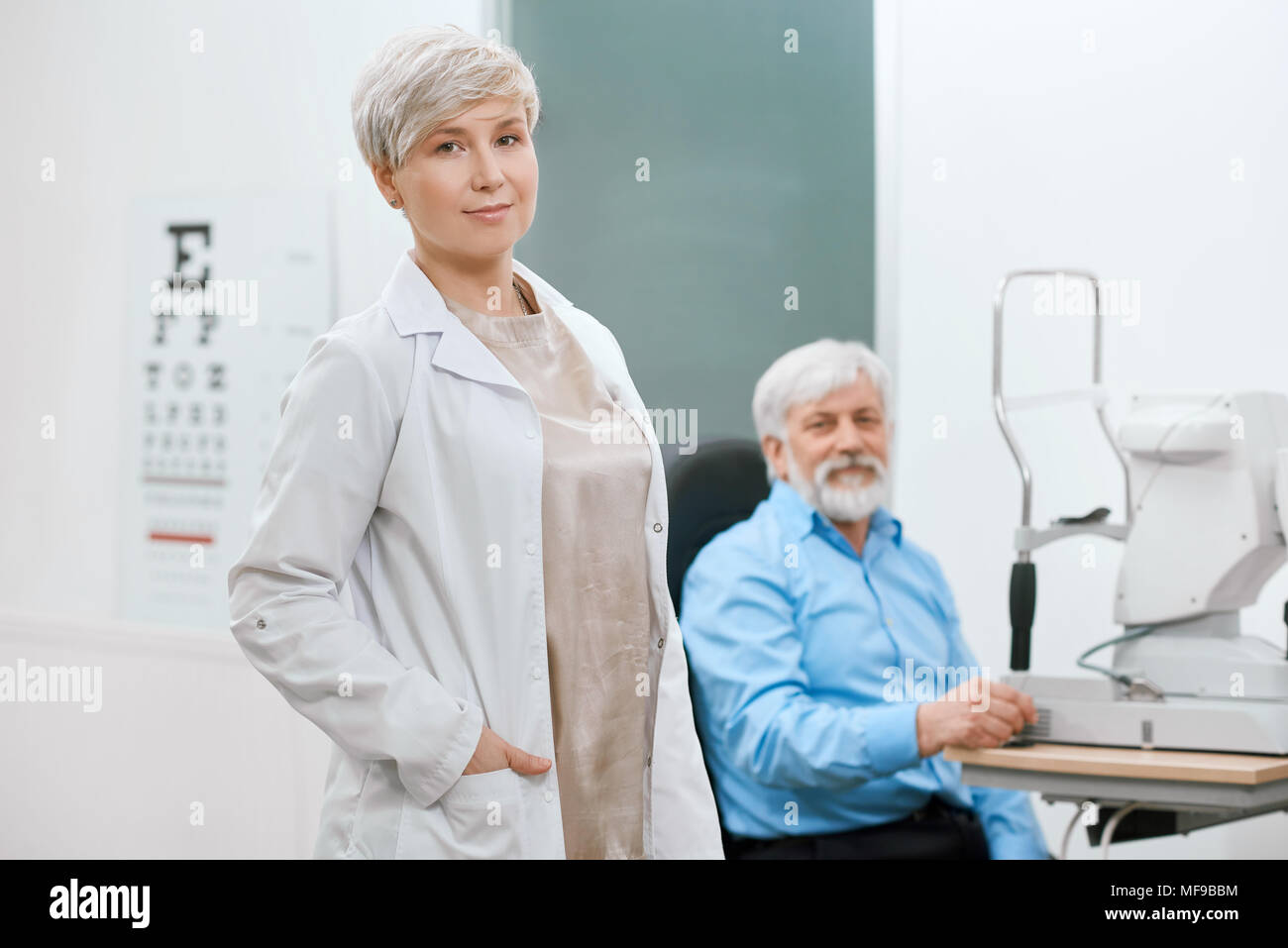 Médecin ophtalmologiste restant en face de l'ancien patient en laboratoire médical d'oculiste. aider à sauver et à améliorer la vision du vieil homme. Un vrai professionnel, expirienced et qualifiés. Banque D'Images