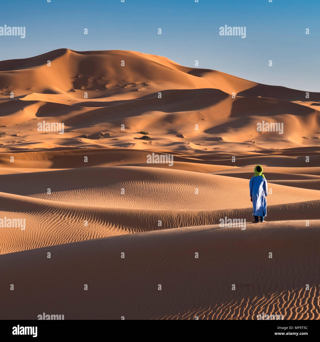 Un homme berbère se situe au bord du désert du Sahara, l'Erg Chebbi, près de Merzouga, Maroc PARUTION MODÈLE Photo Stock