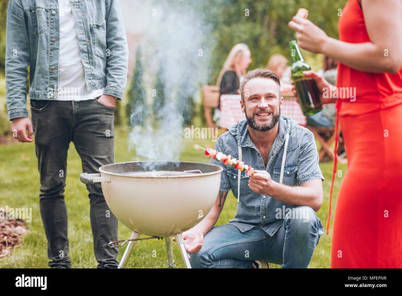 Jeune homme avec un chachlik dans sa main l'accroupissement par un fumeur grill et à la recherche jusqu'à une femme en robe rouge avec d'autres personnes dans l'arrière-plan de manger f Photo Stock