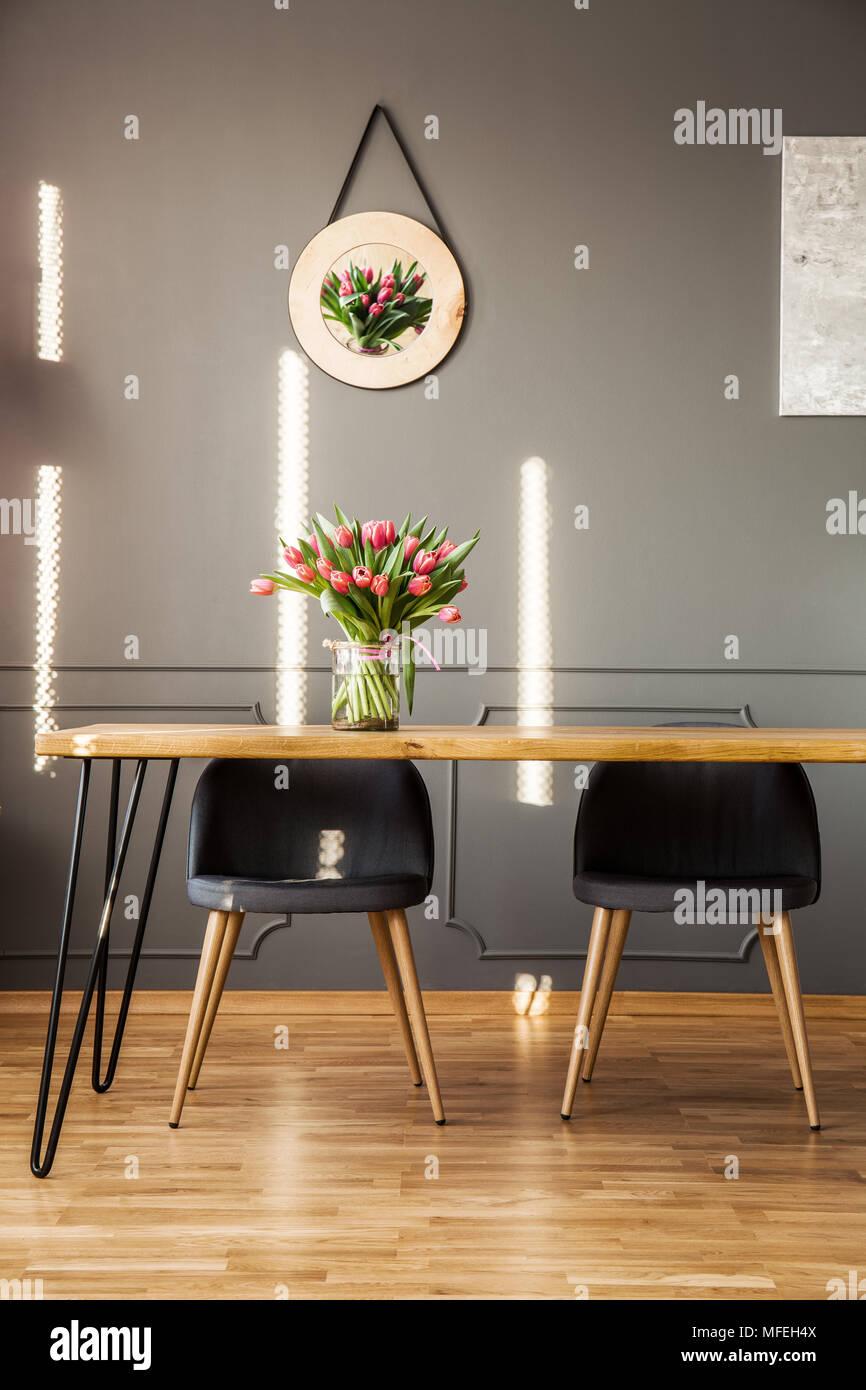 Chaises gris à table en bois avec des fleurs à l'intérieur salle à manger au décor sur le mur Banque D'Images