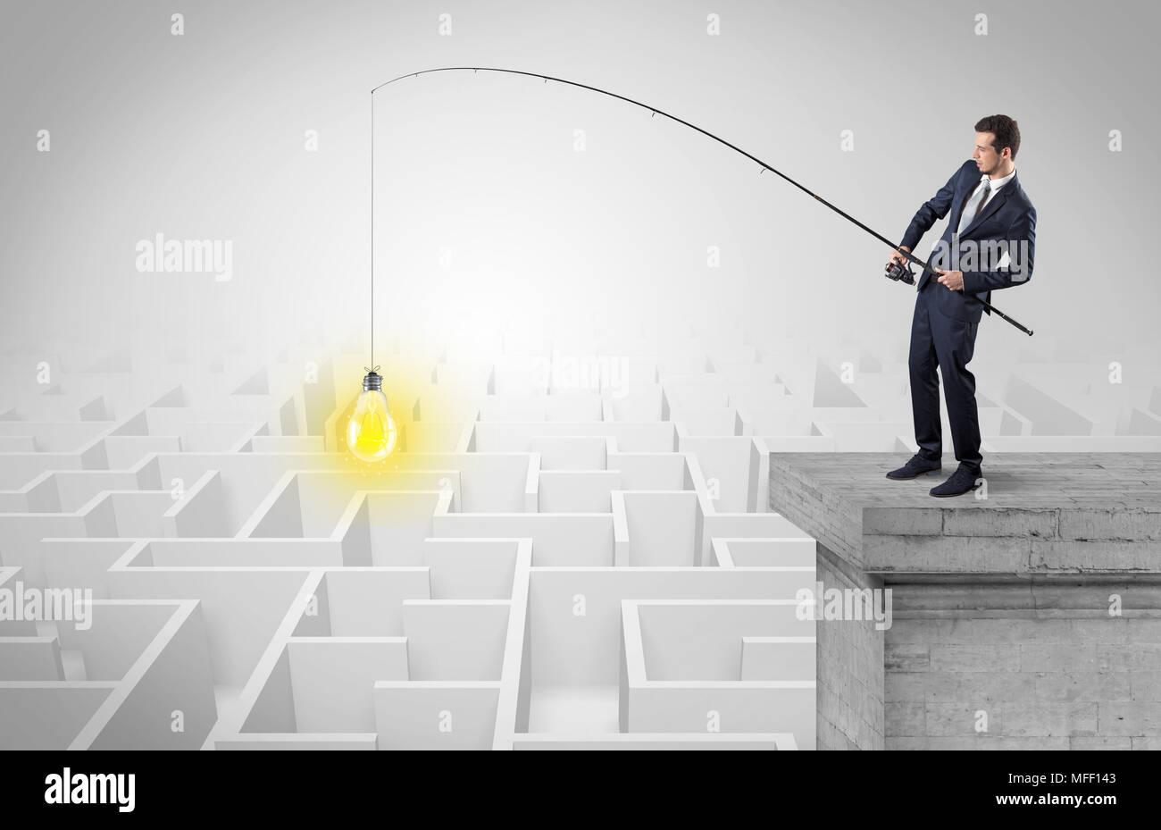 Young businessman pêche à la nouvelle idée concept sur le haut d'un immeuble d'un labyrinthe Photo Stock