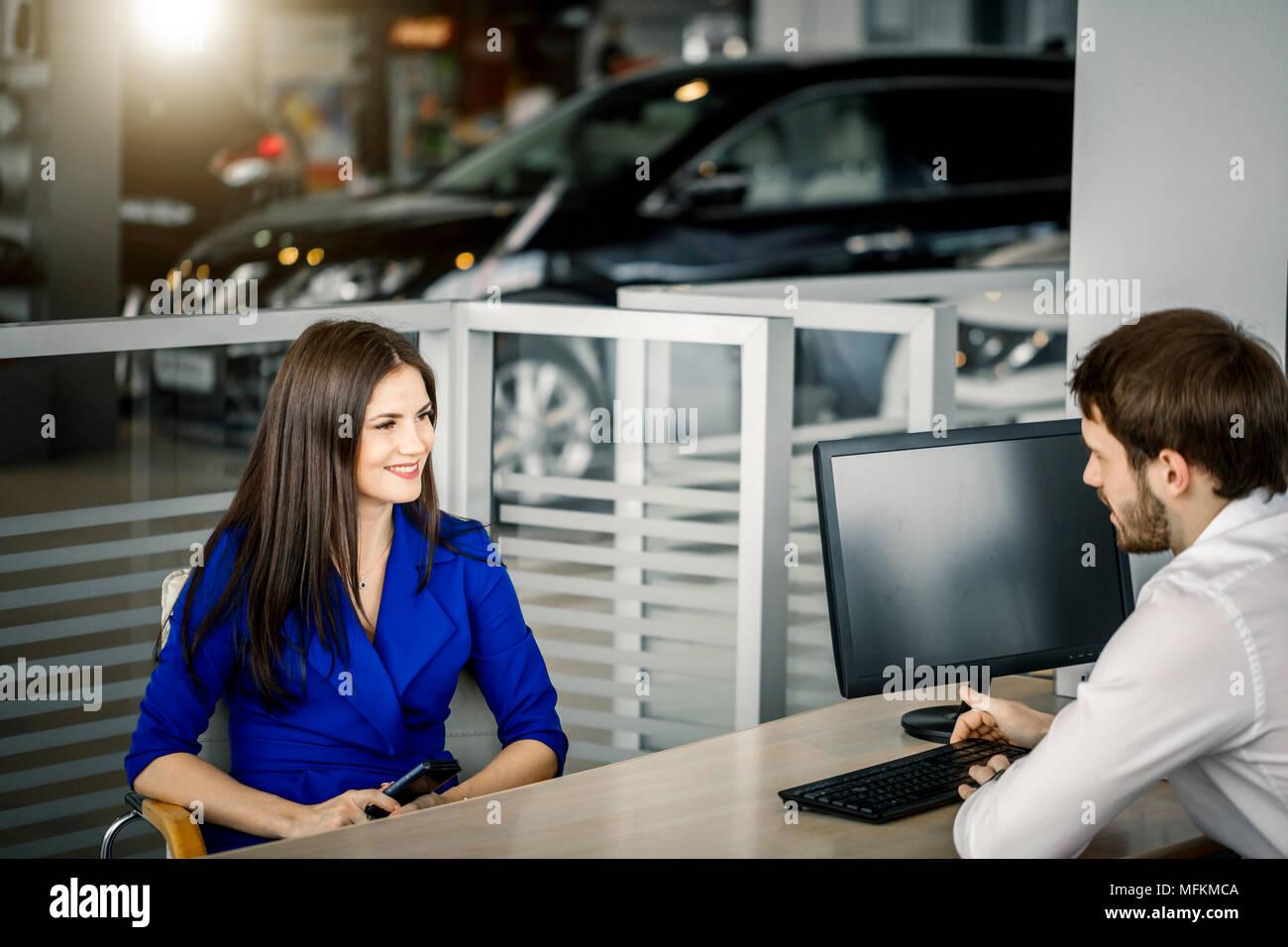 Vendeur parlant de tous les avantages de l'achat de voiture d'une cliente heureuse au concessionnaire d'office Photo Stock