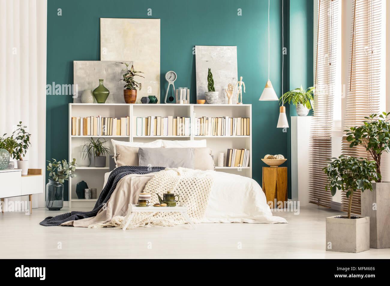 biblioth ques avec des peintures sur le haut comit contre un mur vert fonc blanc derri re lit. Black Bedroom Furniture Sets. Home Design Ideas
