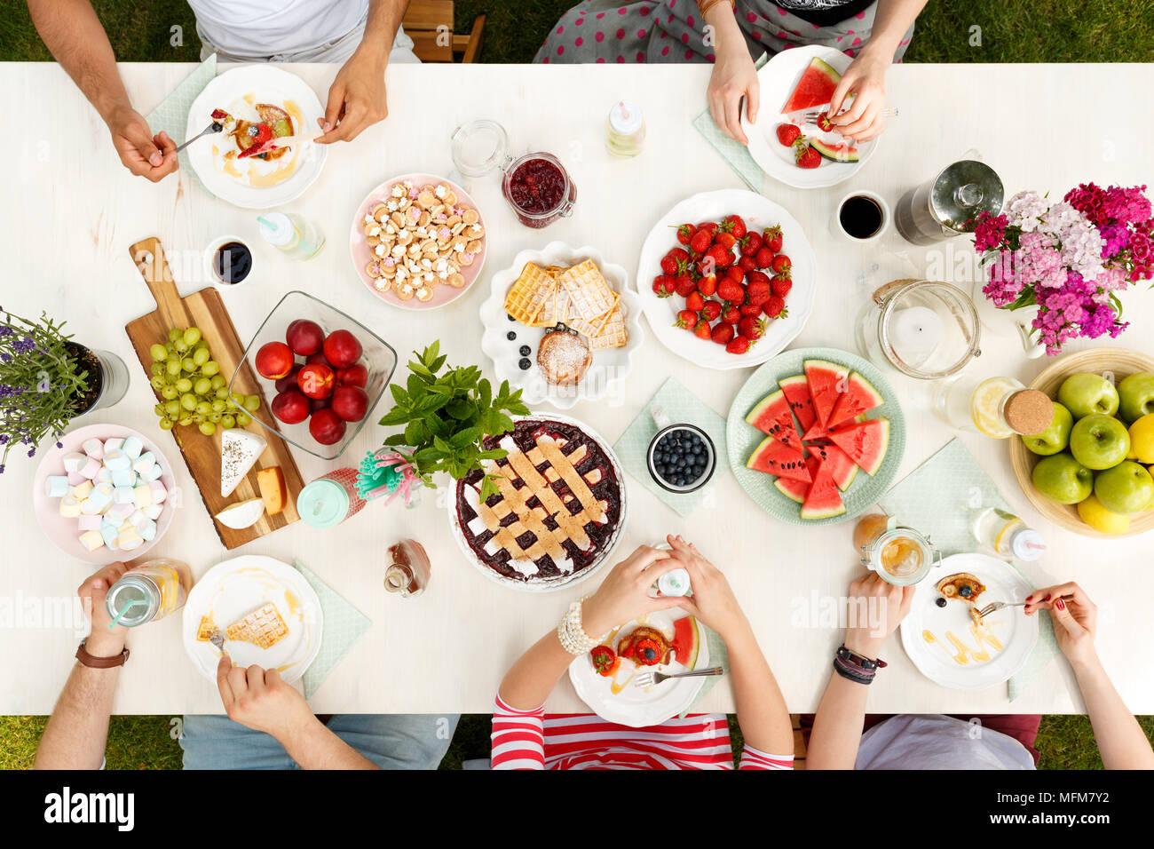 Groupe d'amis de race mixte boire et manger à l'extérieur Photo Stock