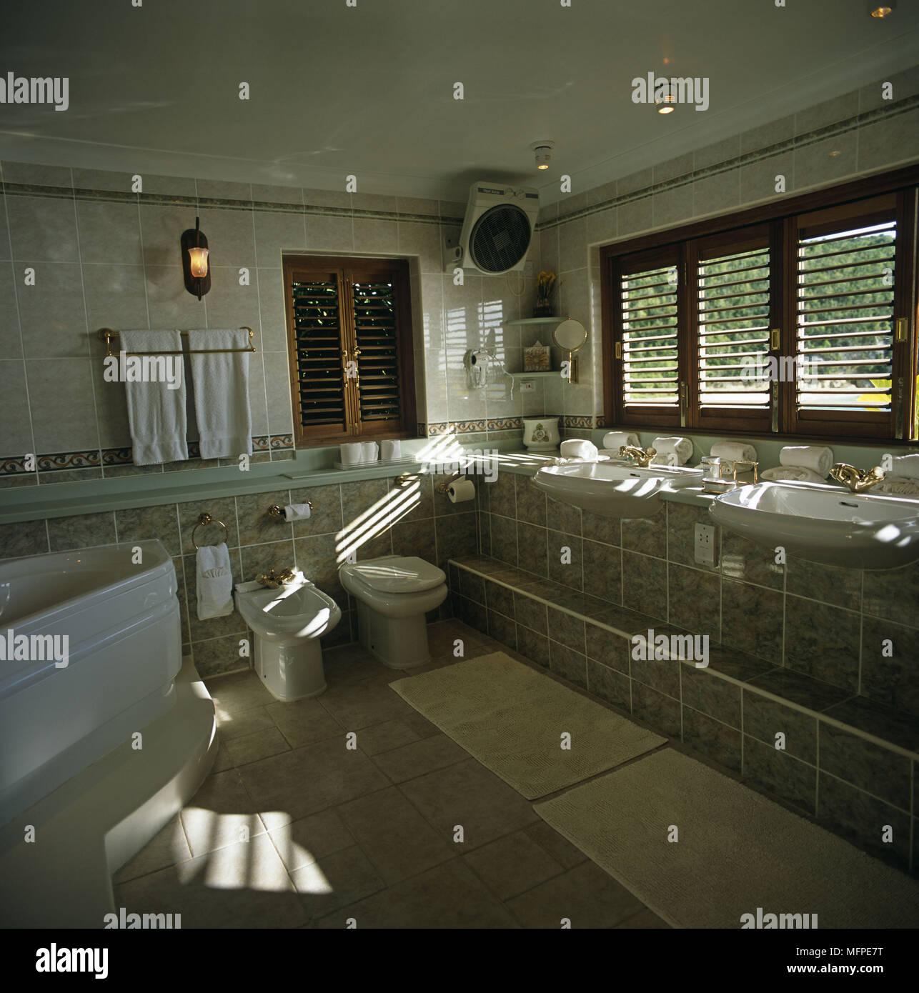 Une salle de bains avec une grande baignoire jacuzzi à côté des ...
