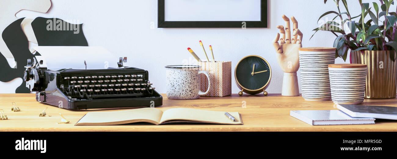 Ouvrez carnet et un stylo posé sur un bureau en bois avec vintage typewriter, plante fraîche et crayons dans boîte de décoration Banque D'Images