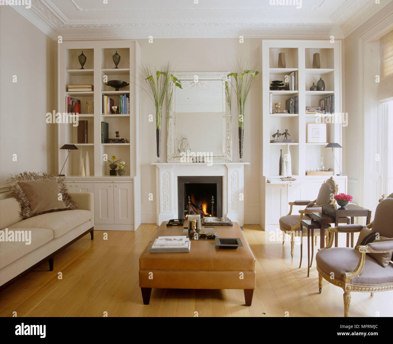 Un blanc moderne salon avec cheminée et le feu allumé ...