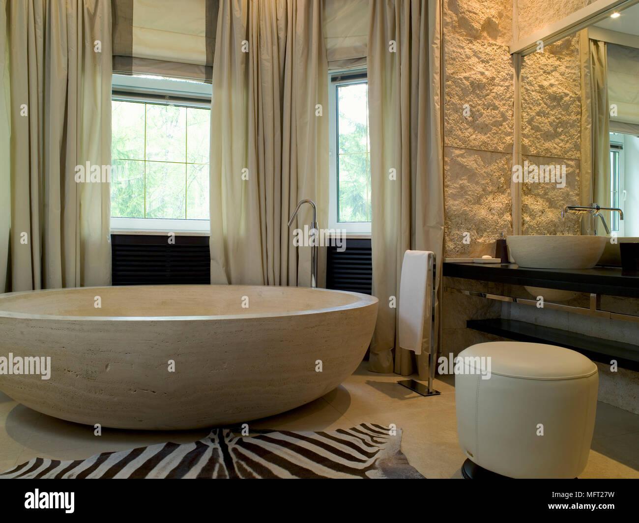 Salle de bains luxueuse avec grande baignoire circulaire à côté de ...